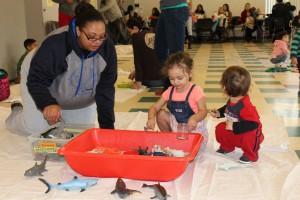 Родители и дети играют на водной сенсорной станции в «Принесите музей на мероприятие Сообщества»
