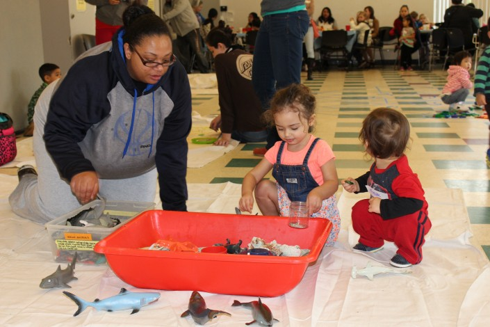 Parents and children play at a water sensory station at the Bring the Museum to the Community event