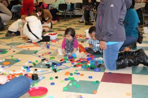 Сотни бутылочных колпачков были собраны через Impact NW. Родители и дети работали вместе, чтобы заниматься искусством в «Принесите музей на мероприятие Сообщества»