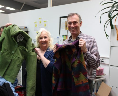 Dianne Denham and Jeff Cogen display donated coats at Impact NW's coat drive.