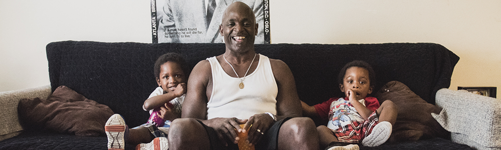 Anthony, Richmond Place Client, sits with his twin sons