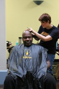 Man receives a haircut from Bishops Barbershop stylists at Impact NW's free haircutting event