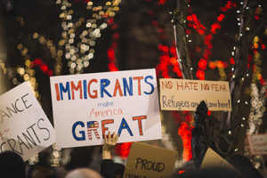 """A rally attendee holds up a sign titled """"Immigrants make America Great"""""""