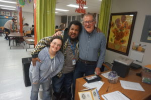 Two participants of Club Impact hang out with founder and volunteer Ralph Gilliam (right) during one of their weekly clubs.