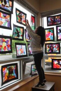 A student at the Beaver Acres Impact NW SHINE Community School hangs up her artwork for display at a student showcase.