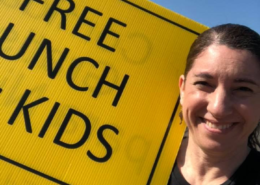 Impact NW Staff Member Holding Free Lunch Sign